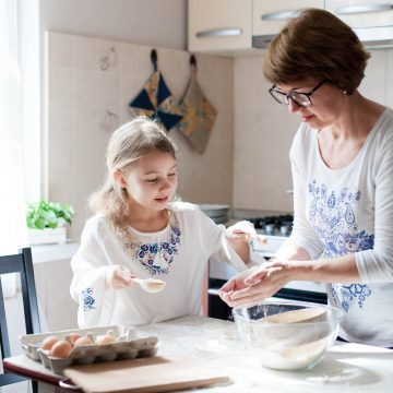 Family is cooking in cozy kitchen at home. Mother and child are making food and meal. Woman and little girl are baking pastries. Cute kid is helping to prepare dinner. Children chef concept.