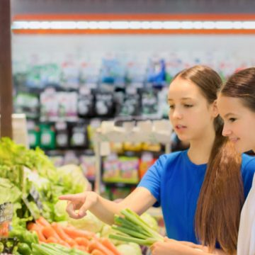 Teen girls shopping in supermarket reading product information. Choosing daily product.